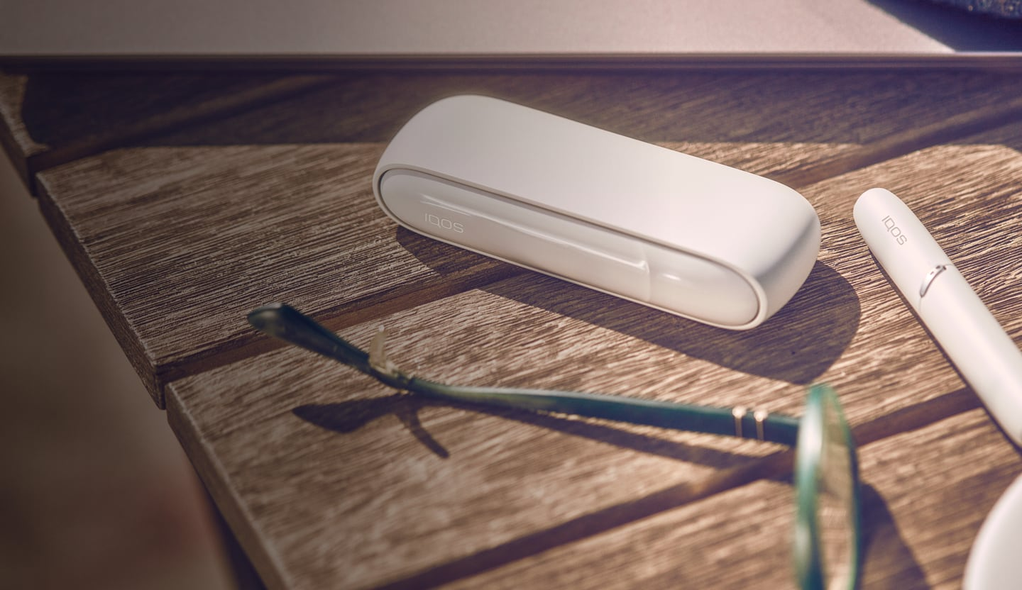 A white IQOS device and holder on a wooden table.