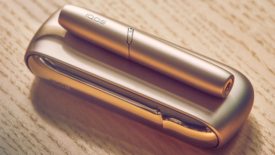 A gold IQOS holder on a closed book.
