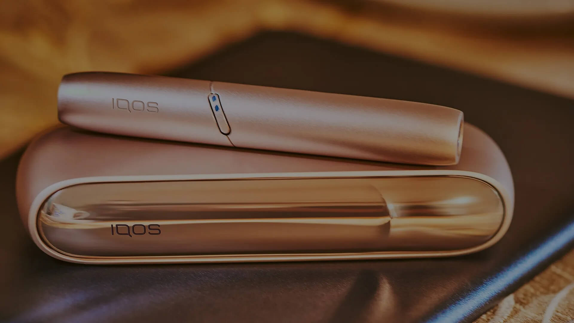 Gold IQOS Duo on a wooden table